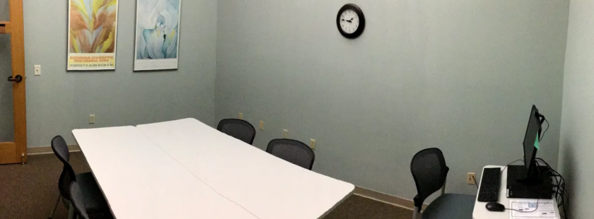 room with two tables, 4 chairs, a clock, a computer, and two paintings on the wall