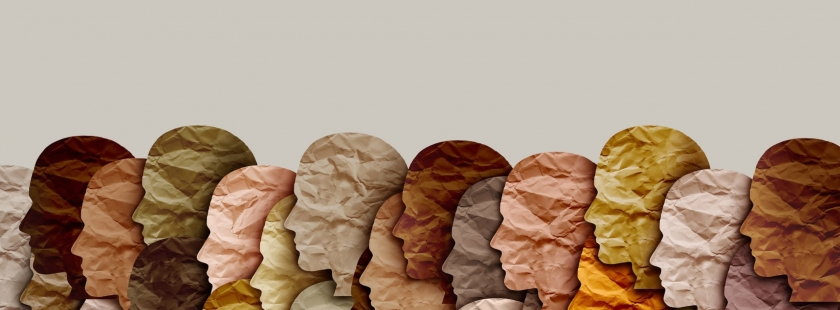 paper cut-out silhouettes of faces in a variety of skin-toned colors
