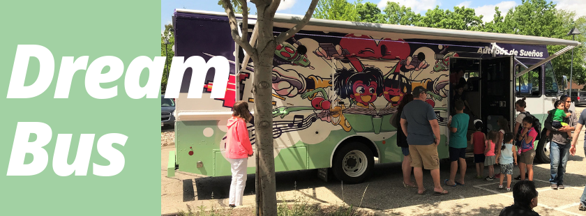 a bookmobile parked in the library parking lot with a line of people waiting to get inside