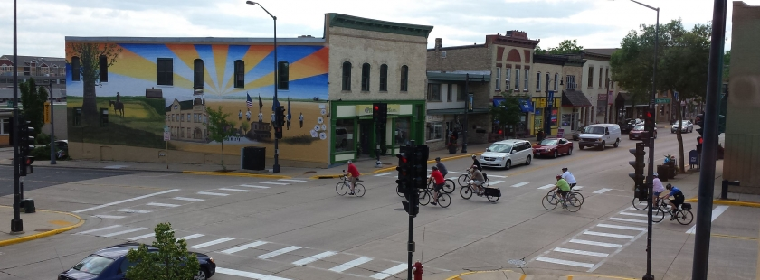 main street crossing with bikes and a mural